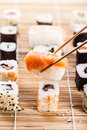 Perfect sushi a salmon nigiri being picked up with chopsticks with different types of maki pieces on a wooden mat in the Royalty Free Stock Image