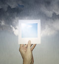 Perfect weather conceptual imagine of a hand holding a picture with a clear sky and a cloudy sky with rain in the background Stock Images
