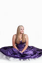 Perfectly purple a pretty caucasian girl sitting on the floor with her full ball gown spread out around her looking up smilingly Royalty Free Stock Photo