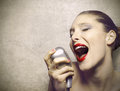 Performance of a beautiful woman singer female with vintage microphone Royalty Free Stock Image