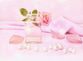 Perfume bottle and flower rose, petals and pearls. Royalty Free Stock Photo