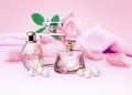 Perfume bottles and flower rose, petals and pearls on pink silk. Royalty Free Stock Photo