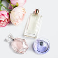Perfume bottles with flowers on light background. Perfumery, cosmetics, fragrance collection. Flat lay