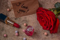 Perfume in a glass bottle, red rose flower and lipstick. Note wi Royalty Free Stock Photo