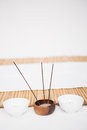 Perfumed candles and incense stem nearby a bamboo mat Royalty Free Stock Image