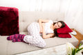 Period pain young woman in the sofa with Stock Photos