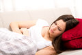 Period pain young woman in the sofa with Stock Photography