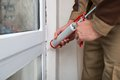 Person applying silicone sealant close up of hands with caulking gun Royalty Free Stock Image