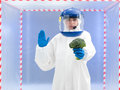 Person in biohazard suit warning about contamination a protective and helmet calling a halt with one hand while holding a broccoli Royalty Free Stock Image