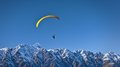 Person in Black Gliding Above Snow Covered Mountain