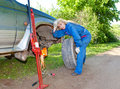 The person in blue working overalls works with a red rack jack about the car changing the punctured wheel woman tries to replace Stock Images