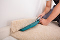 Person Cutting Carpet With Cutter