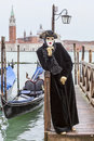 Person disguised venice italy march image of a in a black costume posing on a wooden pier in venice during the venice carnival Royalty Free Stock Photography
