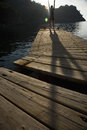Person exercising on jetty distance shot of a wooden by peaceful lake Royalty Free Stock Photos