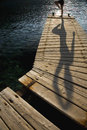 Person exercising on jetty distance shot of a wooden by peaceful lake Stock Images
