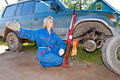The person extended forward the right hand woman in working overalls tries to replace a wheel at an off road car and asks help Royalty Free Stock Image
