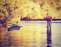 A person fly fishing toned with warm filter Royalty Free Stock Photos