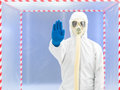 Person with gas mask calling a halt wearing protective suit and in front of confinement tent Royalty Free Stock Image