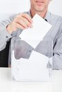 Person inserting ballot in box close up of transparent Stock Image