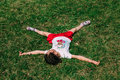 Person lies in a star pose on a grass. Royalty Free Stock Photo