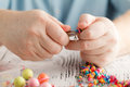 Person making earings from colorful beads and needles Royalty Free Stock Photo
