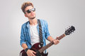 Person playing guitar in studio while wearing sunglasses Royalty Free Stock Photo