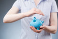 Person protecting savings a young woman a piggy bank with her hands concept about safe deposits or financial future Stock Photo