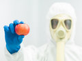 Person in protective suit holding ripe apple Royalty Free Stock Photo