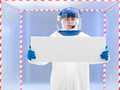 Person in protective suit holding white board and helmet presenting a with both arms front of a confinement tent Stock Image