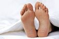 Person s foot in bed close up Stock Image