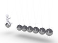 Person sitting on sphere of newton s cradle d a is about to hit the others Stock Image