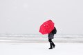 Person in the snow with red umbrella storm Stock Photo