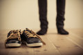 Person Standing Behind Pair of Shoes on Wood Floor Royalty Free Stock Photo