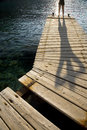 Person standing on jetty distance shot of a wooden by peaceful lake Royalty Free Stock Photo