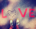 A person standing over the word love on a sidewalk toned with retro vintage instagram filter Stock Images