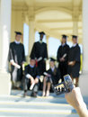 Person video taping young people graduating in caps and gowns Royalty Free Stock Images