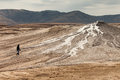 Person walking on mud volcanoes Stock Photo