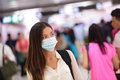Person wearing protective mask in airport against transmissible infectious diseases and as protection against pollution and the Royalty Free Stock Photos