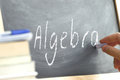 A person writing the word Algebra on a blackboard. Royalty Free Stock Photo