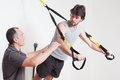 Personal coach explaining suspension training muscular men making with Stock Images