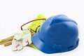 Personal protective equipment or ppe including a blue hardhat yellow vest goggles ear plugs and gloves isolated on a white Royalty Free Stock Image