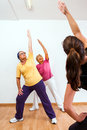 Personal trainer doing aerobic with senior ladies fitness and stretching exercise in gym Royalty Free Stock Photo