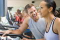 Personal Trainer Encouraging Woman Using Treadmill Royalty Free Stock Photos