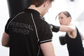 Personal trainer with female client woman working out on punch bag in gym Stock Photos