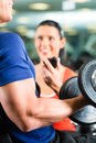 Personal trainer in gym and dumbbell training man or bodybuilder with his fitness the exercising sport with dumbbells closeup Stock Image