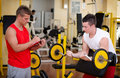 Personal trainer helping client in gym young male during workout on equipment Royalty Free Stock Photography