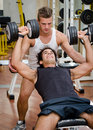 Personal trainer helping client in gym young male during workout on equipment Stock Photo