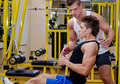 Personal trainer helping client in gym young male during workout on equipment Royalty Free Stock Image