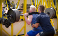 Personal trainer helping client in gym young male during workout on equipment Stock Photos