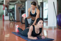 Personal trainer helping girl in leg stretching workout at gym fitness.